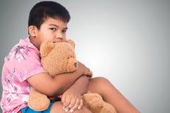 мальчик унылый самостоятельно с коричневым плюшевым медвежонком Стоковая Фотография