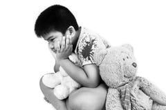 Мальчик унылый самостоятельно с старым плюшевым медвежонком Стоковое Фото