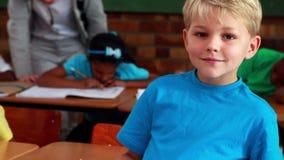 Мальчик усмехаясь на камере во время класса видеоматериал
