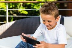 Мальчик усмехаясь на таблетке стоковые изображения rf