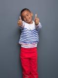 Мальчик усмехаясь с большими пальцами руки поднимает знак стоковое фото rf