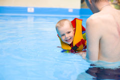 Мальчик учит поплавать в бассейне с отцом Стоковое фото RF