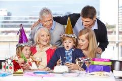 Мальчик дуя вне свеча на дне рождения Стоковое Изображение