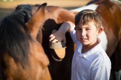 Мальчик холя лошадь в ранчо Стоковое фото RF