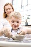 Мальчик царапает из глины на пластичной мастерской Стоковые Фотографии RF