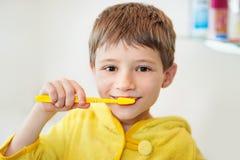Мальчик чистя его зубы щеткой в ванне, усмехаясь, свете - серой предпосылке стоковая фотография