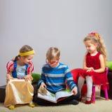 Мальчик читает книгу к маленьким девочкам стоковая фотография rf