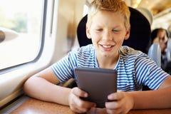 Мальчик читая книгу на поездке на поезде стоковое изображение rf