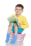 Мальчик читая усаживание книги Стоковые Изображения