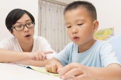 Мальчик читая aloud с tutorship стоковое фото rf