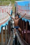 Мальчик шлюпки отбрасывая на рыбацком поселке Камбодже озера сок Tonle Стоковое фото RF