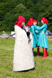 Мальчик Adyghe в черкесском национальном платье играя каннелюру на заднем плане смеясь над девушкой, селективным фокусом Стоковое Фото