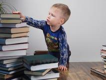 Мальчик e достигает для стога книг Стоковые Изображения