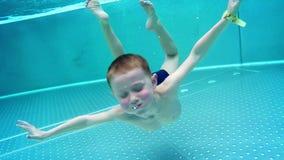 Мальчик Playfull ныряет в горячем бассейне зимы сток-видео