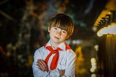 Мальчик Redhead привлекательный одел как советский пионер с красной связью стоковые фото