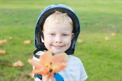 Мальчик Rollerblade давая цветок стоковая фотография rf
