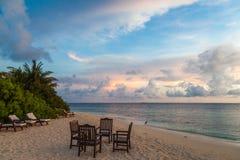 Мальдивы, тропический рай, таблица, стулья и loungers на пляже, восходе солнца Стоковые Фотографии RF