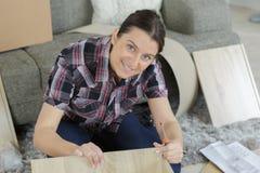 Мебель женщины собирая дома на поле Стоковое фото RF