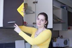 Мебель привлекательной девушки полируя на кухне Стоковые Изображения RF