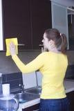 Мебель привлекательной девушки полируя на кухне Стоковое Фото