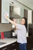 Мебель чистки взрослой женщины на кухне Стоковые Изображения RF