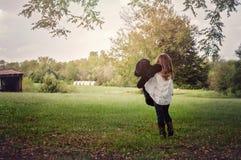 Медведь маленькой девочки заполненный удерживанием на ферме Стоковое Изображение RF