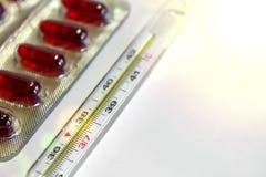 Медицина и термометр на белых предпосылке, высокой температуре, flatlay, пилюльки и термометр, для медицины Стоковые Фотографии RF