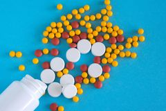 Медицина Капсулы цвета около бутылки таблетки на голубой предпосылке, космосе экземпляра взгляда сверху стоковая фотография rf