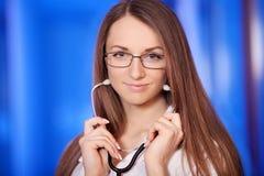 Медицина Привлекательный женский доктор на фронте, голубая предпосылка, красивая женщина, молодой доктор, вплетает Стоковое Изображение RF