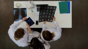Медицинская бригада обсуждая диагноз рентгеновского снимка отображает используя специальную таблетку стоковые изображения