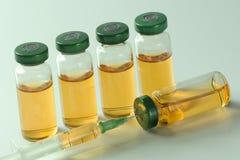 Медицинские ампулы с вакциной и шприцем на белой предпосылке Стоковые Фотографии RF