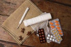 Медицинские повязка, пилюльки и термометр на деревянной предпосылке Взгляд сверху Стоковые Фотографии RF