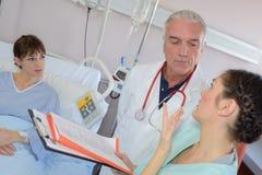 Медицинские работники в dscussion на терпеливом уходе за больным ` s Стоковая Фотография