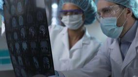 Медицинские работники смотря человеческий мозг MRI, обсуждая результат для того чтобы установить диагноз акции видеоматериалы