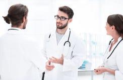 Медицинский персонал обсуждает в современной палате стоковое фото