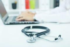 Медицинский стетоскоп лежа на крупном плане стола пока доктор медицины работая в предпосылке Здоровье, защита Стоковое Изображение