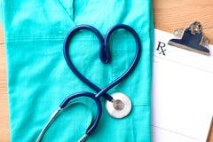 Медицинский стетоскоп переплел в форме сердца лежа на терпеливом крупном плане формы доктора списка и сини истории болезни Стоковые Изображения RF