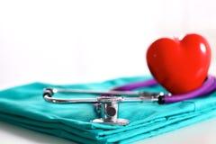 Медицинский стетоскоп переплел в форме сердца лежа на терпеливом крупном плане формы доктора списка и сини истории болезни Стоковые Фото