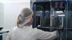 Медицинский ученый исследования вирусологии работает с маской зажим Ученый принимает вне пробирки от холодильника Она работает стоковые фото