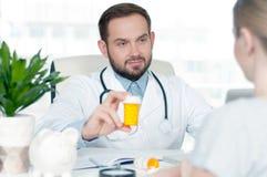 Медицинское обслуживание Доктор давая опарник пилюлек к пациенту Стоковое Фото