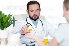 Медицинское обслуживание Доктор давая опарник пилюлек к пациенту Стоковые Изображения RF