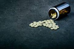 Медицины, дополнения в стеклянной бутылке Пилюльки разливая вне от стеклянной бутылки Предпосылка Medicineфармация Стоковые Фото