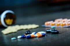 Медицины, дополнения в стеклянной бутылке Пилюльки разливая вне от стеклянной бутылки Предпосылка Medicineфармация Стоковая Фотография