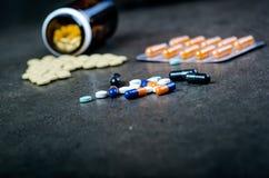 Медицины, дополнения в стеклянной бутылке Пилюльки разливая вне от стеклянной бутылки Предпосылка Medicineфармация Стоковое Изображение