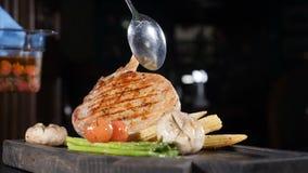 Медленно съёмка видео с едой Шеф-повар в перчатках украшает готовое мясное блюдо со съеденным помидором Стекло с овощами на видеоматериал