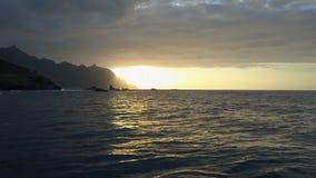 Медленный полет над океанскими волнами смотря на красивый заход солнца и горы на горизонте Воздушная съемка трутня красивого захо видеоматериал