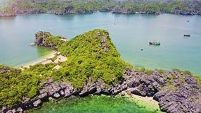 Медленный полет над скалистым островом с круглыми лагуной и маленьким городом сток-видео