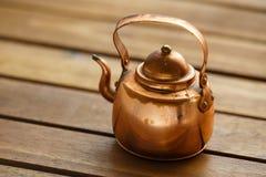 Медный старый поцарапанный винтажный чайник kitchenware посуды на таблице стоковые изображения rf