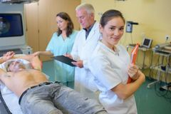 Медсестра и доктора с пациентом человека на кровати Стоковые Фото