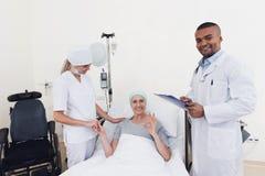 Медсестра и доктор стоят рядом с пациентом с раком Доктор держит ее рентгеновский снимок Стоковое Изображение RF